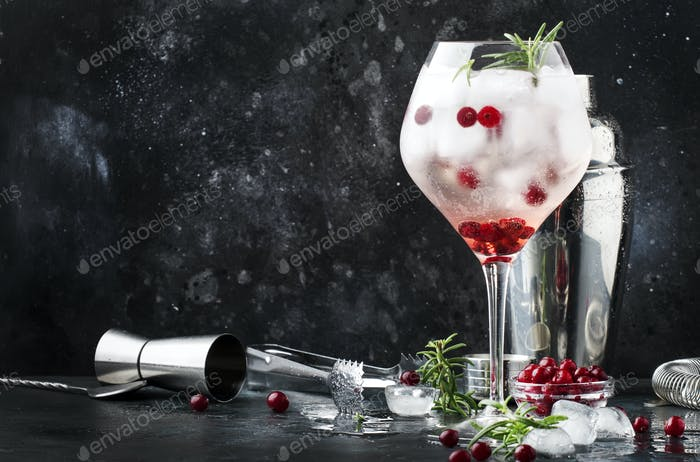 Cranberry cocktail with ice, rosemary and berries in big wine glass, bar tools