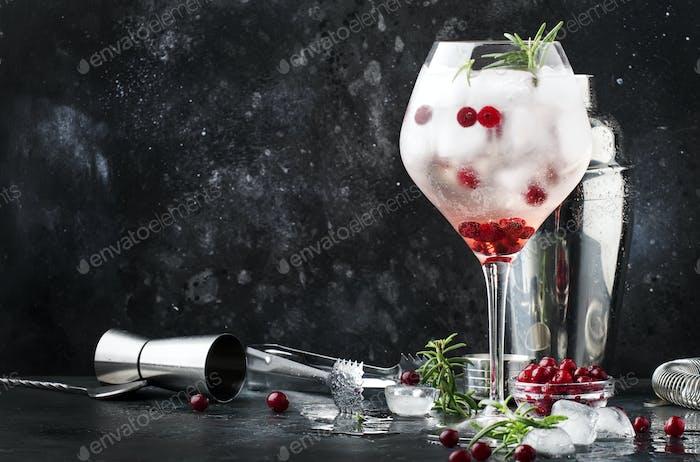Cranberry-Cocktail mit Eis, Rosmarin und Beeren im großen Weinglas, Bar-Tools