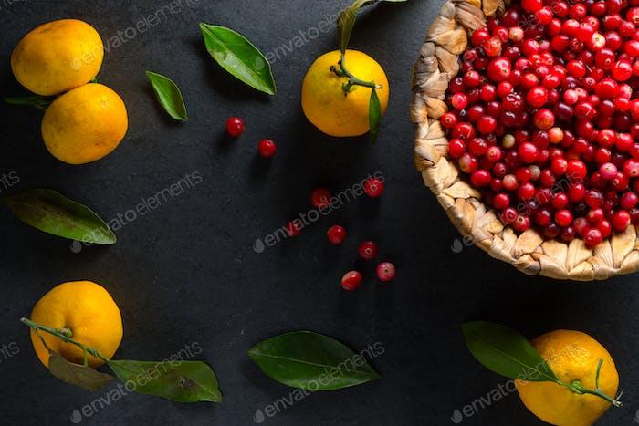 Gelbe Mandarinen mit Blättern und Preiselbeeren in einem Korb auf einem grauen Stein Freiraum