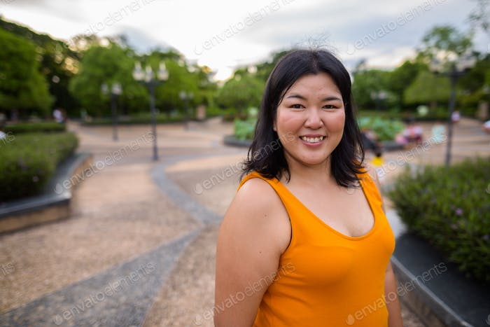 Beautiful overweight Asian woman relaxing and smiling in park