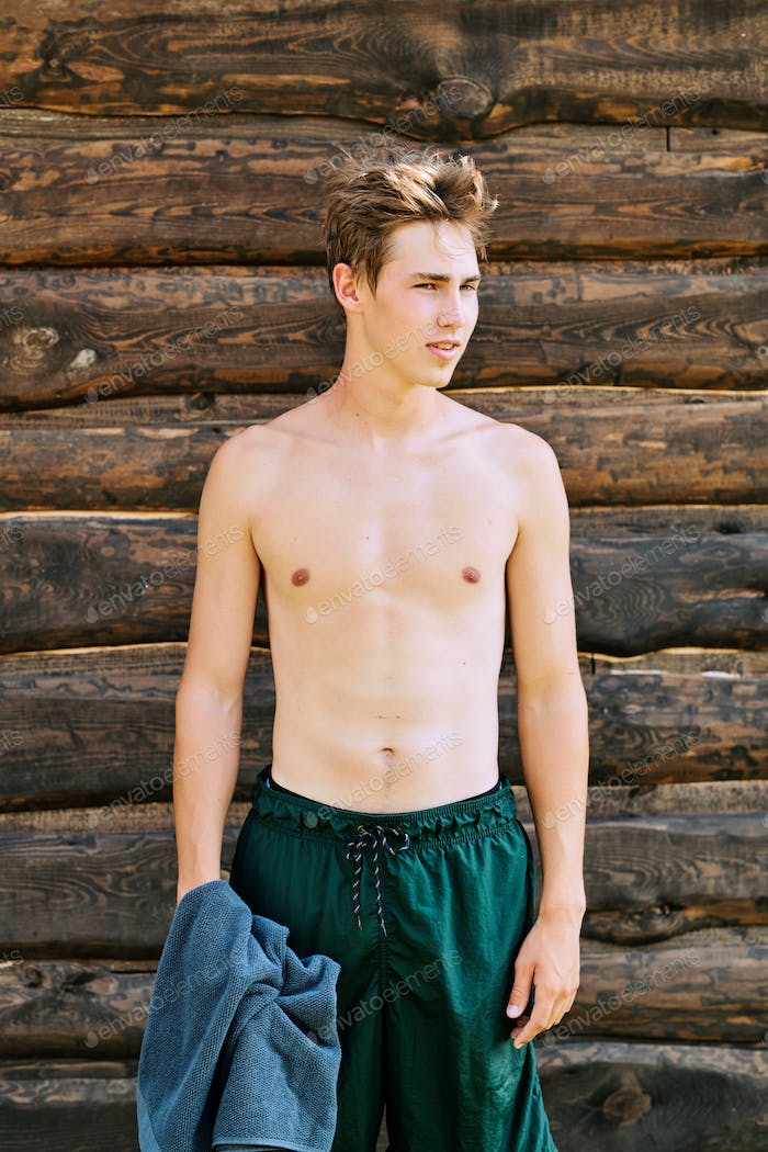 Young topless male surfer in green wet shorts holding towel over wooden wall