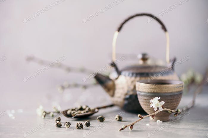 Traditional asian tea ceremony arrangement. Flat lay of iron teapot, cups and blooming cherry tree
