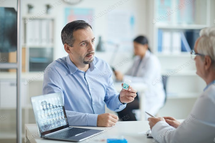 Patient holding pills and talking to doctor