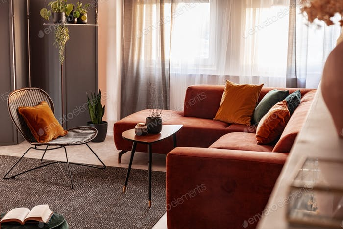 Small coffee table in front of comfortable corner sofa in autumn colored living room interior