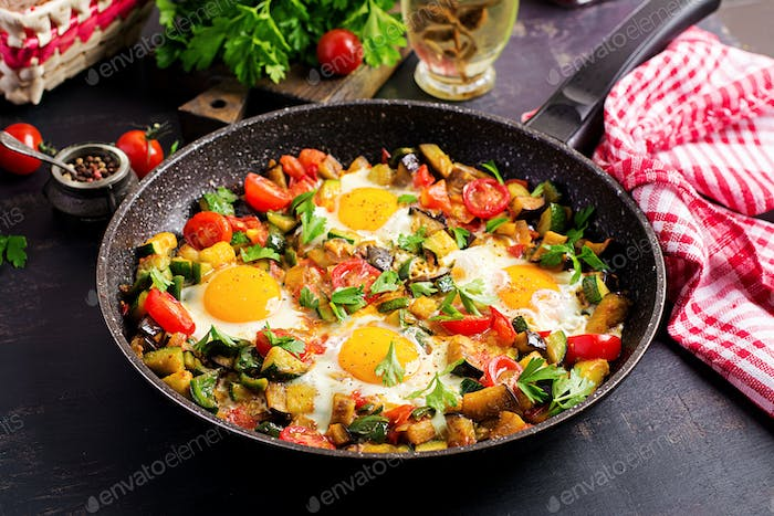 Late breakfast - fried eggs with vegetables. Shakshuka. Arabic cuisine. Kosher food.