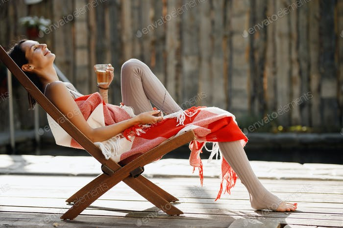 Young woman wrapped in a red and white plaid sits in a folding chair with glass of water in her hand