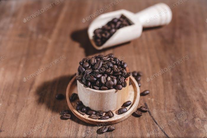 Kaffeebohnen auf Holztasse und Holzschaufel