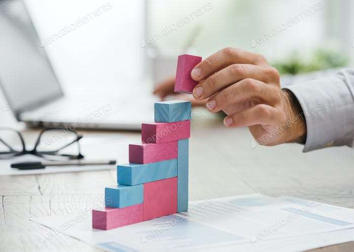 Businessman building a growing financial graph