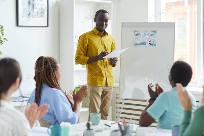 Smiling African Man Standing by Whiteboard in Meeting