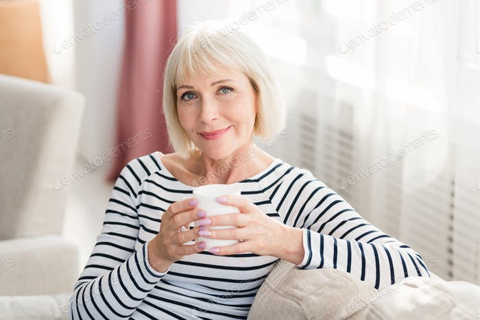 Mature woman drinking fresh morning coffee at home