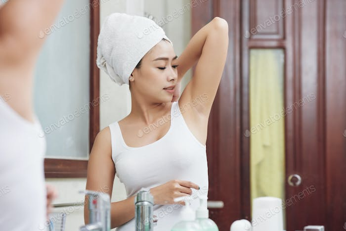 Young ethnic woman with hand raised in bathroom