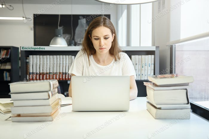 Intelligentes und intelligentes junges Universitätsmädchen, das auf der Tastatur ihres Notebooks tippt