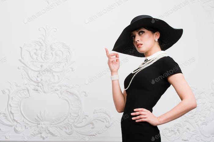 Porträt einer schönen jungen Frau im Retro-Stil in einem eleganten schwarzen Hut und Kleid über Luxus
