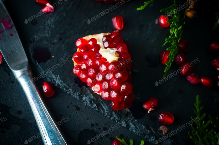 Halb Granatapfel und Samen ein Zweig der Fichte
