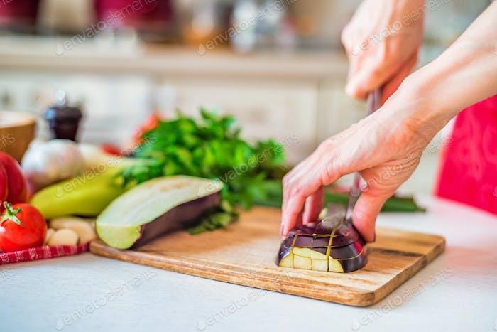 Cerrar la Mano Mujer con cuchillo corta berenjena en Panel de De madera en la Cocina. Cocinar verduras