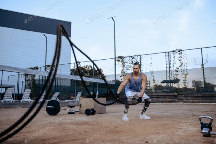 Athletic man with ropes, street workout, crossfit