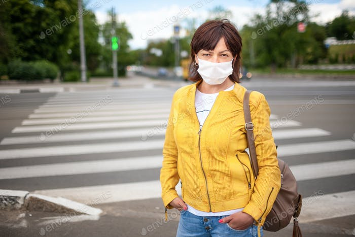 Adult pretty woman in casual clothes and bag with a protective mask