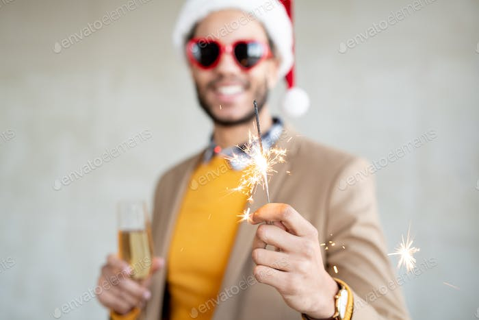 Hand of happy young businessman holding flute of sparkling bengal light at party
