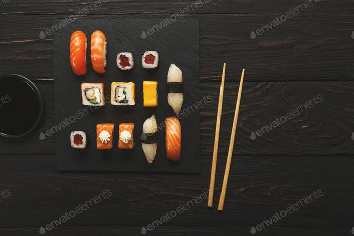 Set of salmon sushi and rolls on black wood background, top view