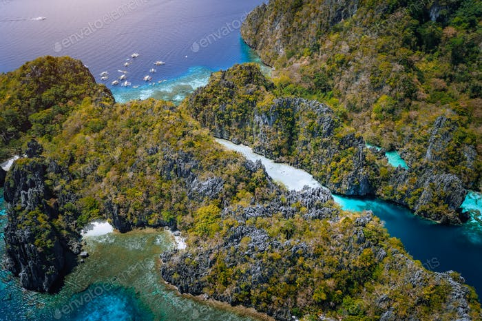 Aerial drone of entrance to big lagoon with limestone cliffs and blue water. Miniloc island, Marine
