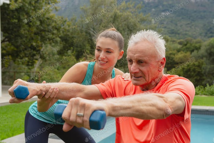 Caucasian female trainer assisting active senior Caucasian man to exercise with dumbbells