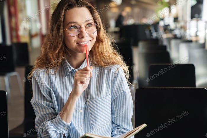 Image of cheerful woman smiling and writing on planner while sitting