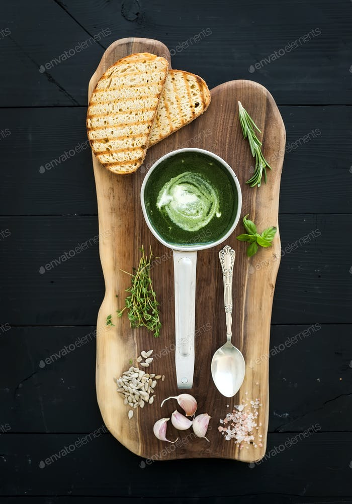 Homemade green spinach cream-soup in a metal scoop with grilled bread slices