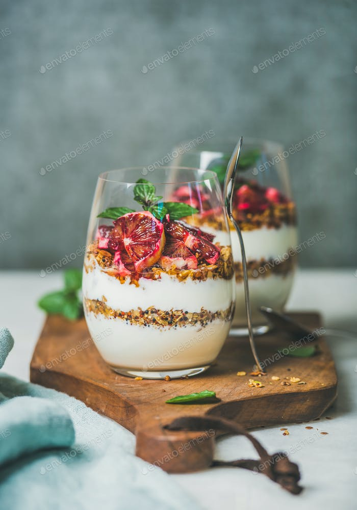 Healthy breakfast glasses with yougurt, granola and orange