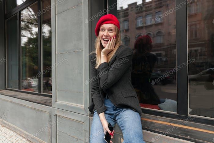 Erstaunt attraktive junge blonde Frau mit roter Maniküre