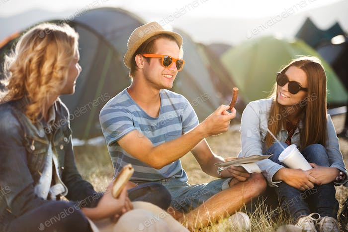 Teenagers sitting on the ground in front of tents and eating