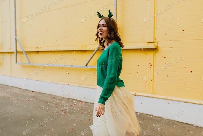 Cheerful caucasian girl wears christmas headgear walking down the street. Outdoor photo of woman we