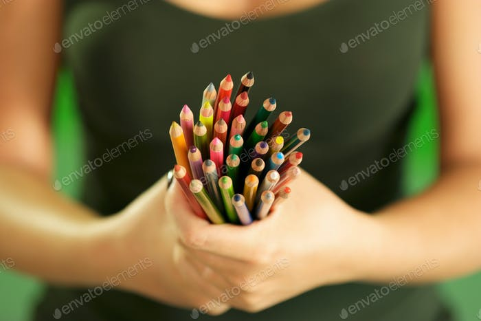 Young Female Painter Holding Colored Pencils At Camera