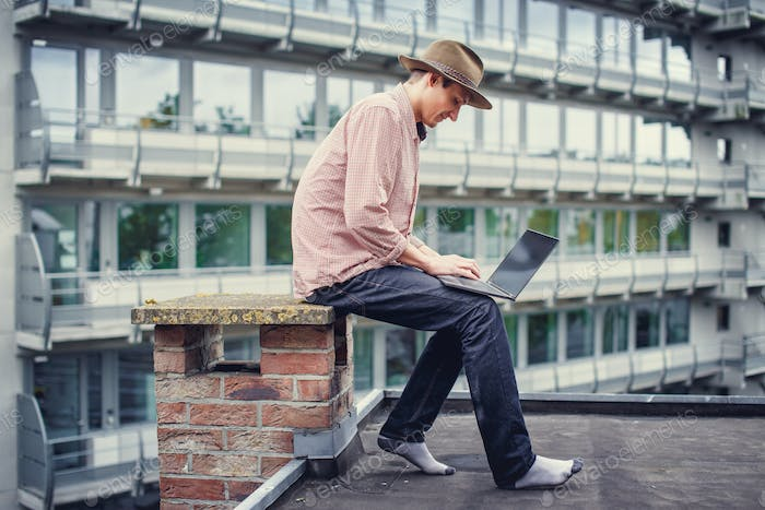A man using laptop on the roof.