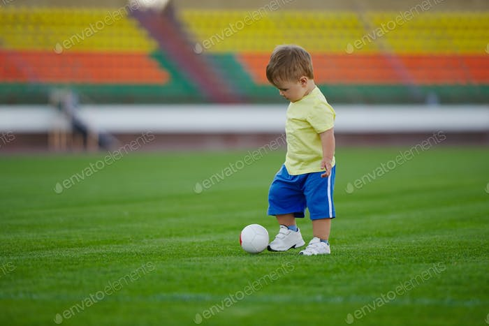 little funny boy on football stadium