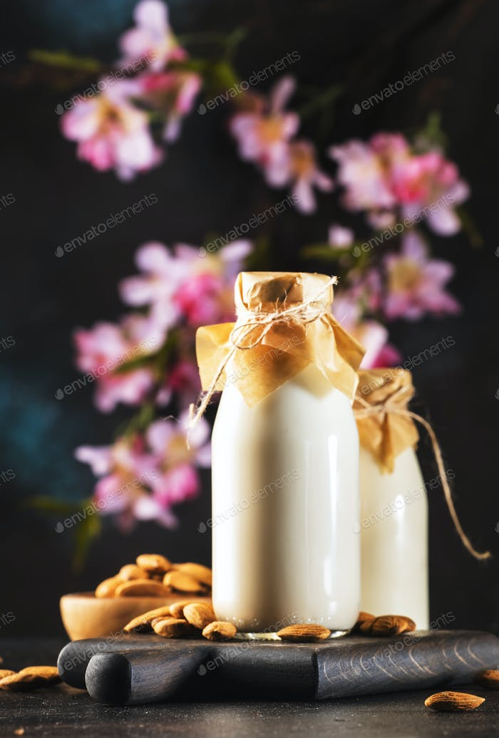 Almond vegan alternative milk with nuts on brown table with
