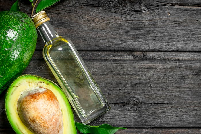 Avocado with leaves and a bottle.