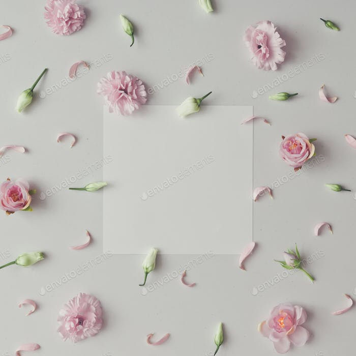 Creative pattern made of violet and pink flowers with paper card copy space. Flat lay.