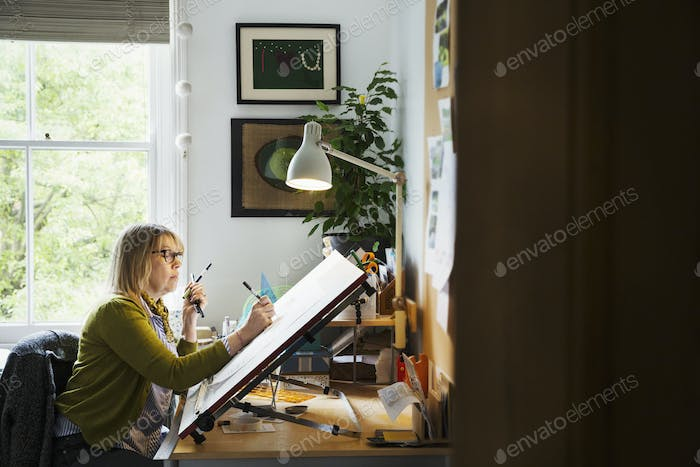 Woman sitting at a drawing board, drawing with a fineliner.