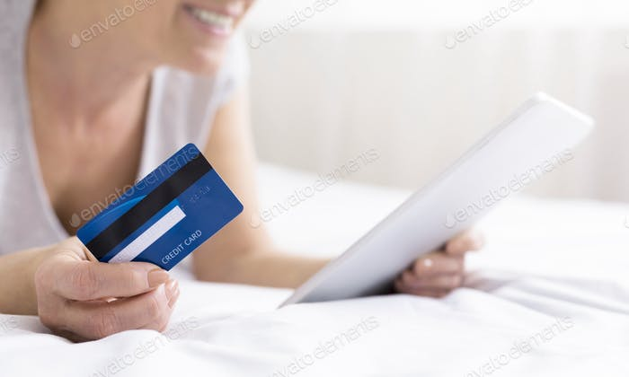 Seenior woman in bed doing online shopping with digital tablet