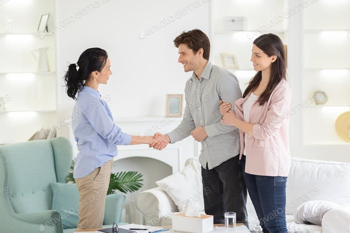 Psychologist and thankful couple handshaking in office