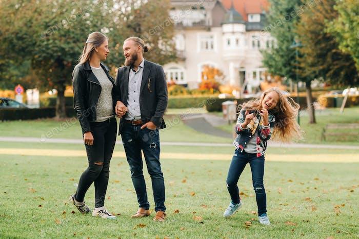 A happy family of three runs through the grass in Austria's old town.A family walks through a