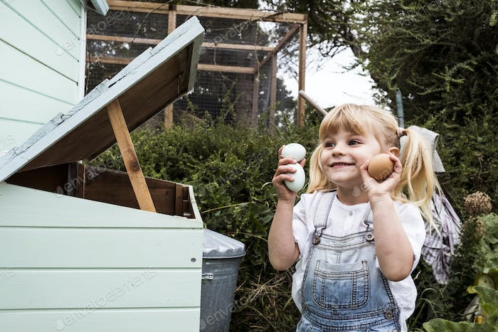 Smiling girl standing outdoors, holding three freshly laid eggs in her hands.