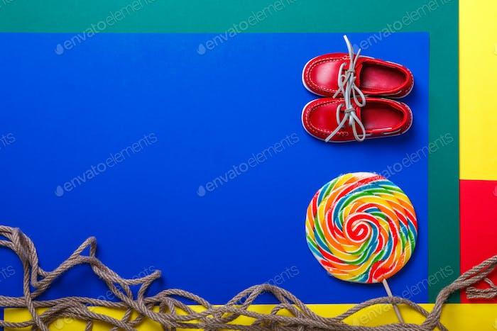 Kleine rote Bootsschuhe in der Nähe von großen bunten Lollipop