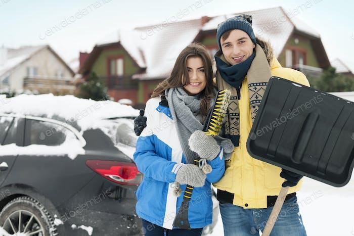 Glückliches Paar sind bereit, Auto von Schnee zu reinigen