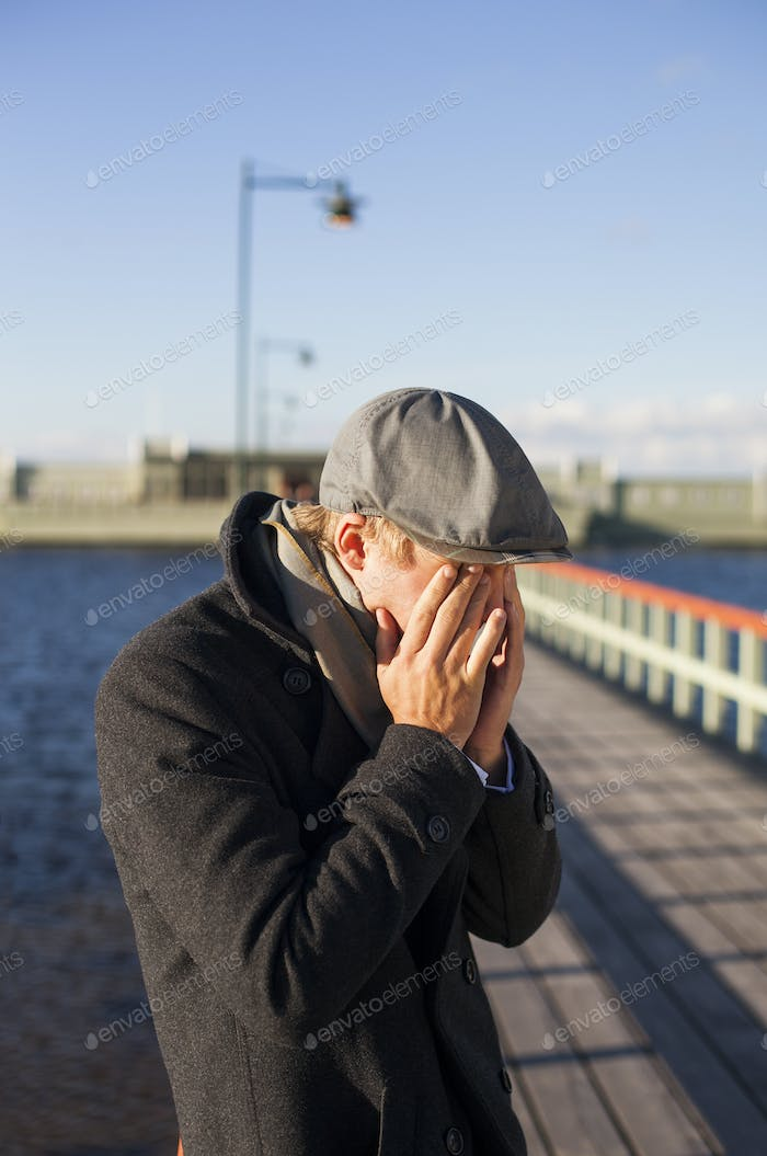 Young man covering eyes with hands while standing on pier