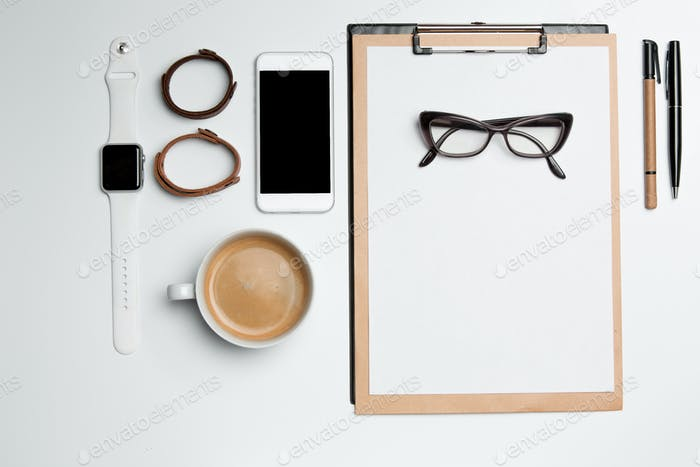 Office desk table with cup, supplies, phone on white