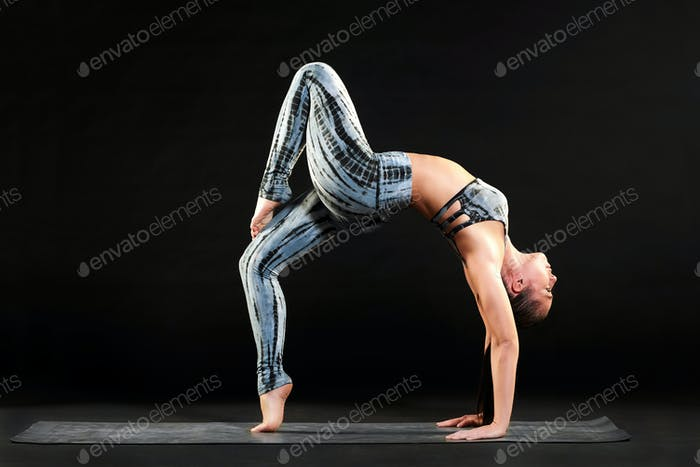 Fit healthy woman doing a one legged wheel pose