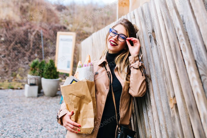 Cute young woman with glasses and red lips leaned on the fence holding foodstuffs from the store. Ch
