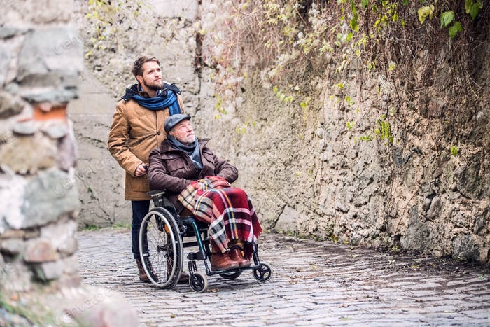 Senior father in wheelchair and son on a walk in old town.