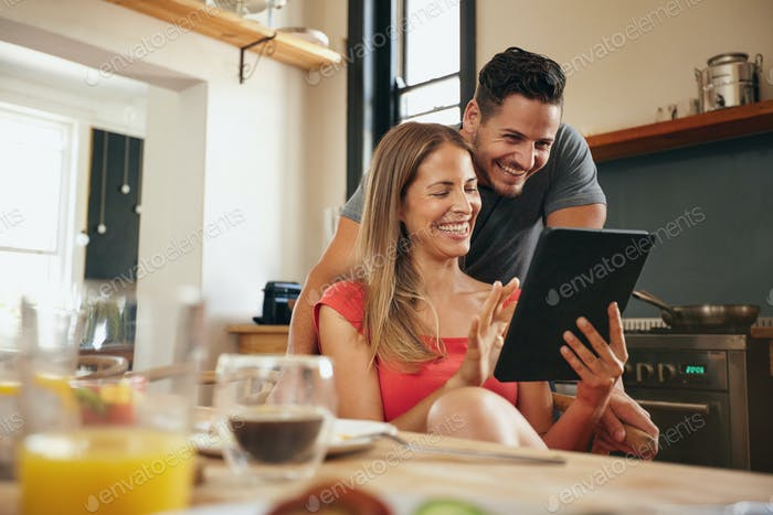 Happy young couple using a digital tablet in morning